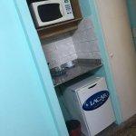 Pequeño kitchenette en la habitación, con heladera y microonda.