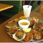 Platter of baked oysters with hot melted butter and crackers.