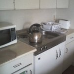 Kitchenette with microwave, small fridge, 2-burner electric stove, toaster, sink but no coffee m