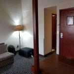Dated lounge (left), open door to bathroom (centre) and external door (right)