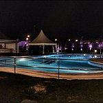 Vista nocturna zona de terraza y piscina
