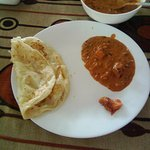 The plate served with Paneer Butter Masala and Butter Paratha.
