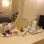 Fresh fruit, welcome gift and bath robe in mirror reflection.