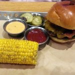 ultimate bacon burger with a side of corn on the cob