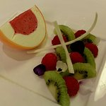 Frozen Orange Parfait with a Raspberry Sorbet Centre, with fresh Raspberries & Kiwi fruit.