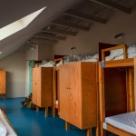 8-bed dorm with six bunk beds on the right and two single beds on the left.