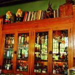 A couple of dwarves on top a spirits Cabinet behind the bar