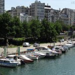 Many smaller boats moored up along Canal Saint-Martin, with scenic paths and roads along the can