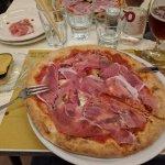 Pizza con base pomodoro senza mozzarella, con bufala, alici, capperi, pomodori secchi e crudo.