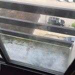 Small unsafe balcony with grime and mold covering the windows.