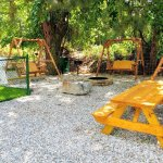 Group relaxing area with stone fire pit, log swings, charcoal grills & fenced in spot for your p