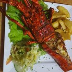 Grilled lobster w/ some french fries and fresh salad.