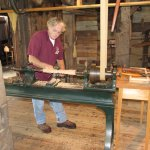 Tour guide demonstrating wood lathe, belt driven from water turbine shaft.
