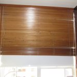 Room darkening shade behind the wooden blinds