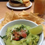 Smashed avocado with organic corn chips with Polish burger in the background