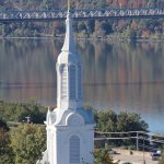 A great vies of a church steeple against fall foliage background.