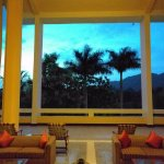 The upstairs lounge at nightfall, with view of forest and mountains