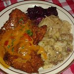 Breaded pork cutlet with paprika sauce, warm potato salad, white and red wine-braised cabbage