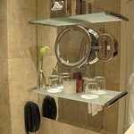 Shelf with glasses and great magnified makeup mirror.
