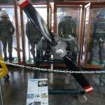 Antriebsmaschine mit Luftschraube und dahinter PIloten-/Druckanzüge.
