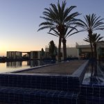 Expansive hotel courtyard with outdoor pools at sunset