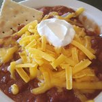 Bowl of Chili loaded with onions, cheese and sourcream