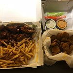 Wings and boneless bites combo with fries and a portion of fried pickles.