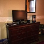 King bed room: TV, coffee maker, multi plug outlet by bed, chair and side table.