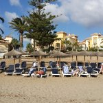 Stood at the shore line looking back at the resort. Sun loungers in foreground.