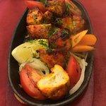 Chicken tikka starter . Tender chunks of marinated chicken served on a sizzling platter .