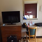 Small TV, desk area and only one chair in room