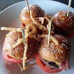 four mini-cheeseburgers with onion straws
