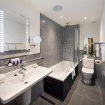 Bathroom with bath and shower over bath