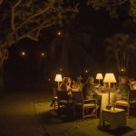 Dining out in the oasis with lanterns in the trees