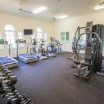 Fully equipped fitness center with cardio machines, weight machines and free weights