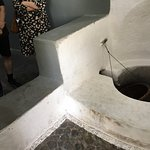 couple of guests standing where the grapes are crushed the old fashioned way and drain into the