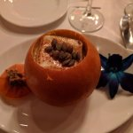 winter squash soup served in a small pumpkin with toasted pumpkin seeds and a brûléed marshmallo