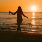 drunk-girl-with-a-bottle-of-wine-in-hand-walks-along-the-beach-at-sunset_hutnajl5_thumbnail-smal