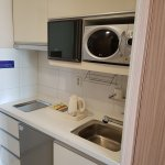 Mini kitchen with amenities, microwave, hot watr boiler, cabinets and utensils.