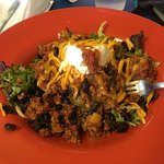 This colorful spring green salad is topped with delicious, tangy Picadillo, beans, sour cream an