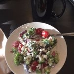 Broccoli salad on china with cow goat cheese & grapes