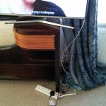 Television balanced on narrow drawer of dressing tables and extention lead.