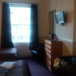 Large window over looking the front street, small TV and lots of storage/drawers and wardrobe.