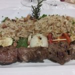 Brochete de cordero con arroz pilaf con almendras y vegetales grillados
