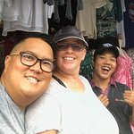 Me, my wife, and our Good Bali Driver Sofyan hiding in a store while it poured down rain!