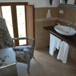 Large bathroom with a comfortable armchair.