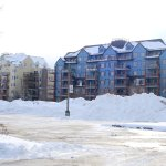 Apartment blocks behind mountains of snow cleared from hotel car park