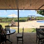 desayunando con vista a la piscina y el mar de fondo