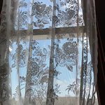Beautiful lace curtains grace the tall windows.
