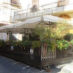 Delightfully shaded outside tables on a raised terrace on a quiet street.